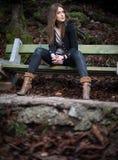 Mujer joven que se sienta en el banco en bosque Imagen de archivo