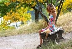 Mujer joven que se sienta en el banco y que acaricia un gato Imágenes de archivo libres de regalías