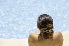 Mujer joven que se sienta en el borde de la piscina Imagenes de archivo