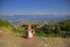 Mujer joven que se sienta en el borde del acantilado que mira sobre la vista expansiva de llanos y de montañas fotografía de archivo libre de regalías