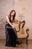 Mujer joven que se sienta en el brazo Imagen de archivo