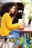 Mujer joven que se sienta en el café al aire libre usando el ordenador portátil imagenes de archivo