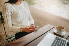 Mujer joven que se sienta en el café al aire libre usando el teléfono móvil Imagen de archivo