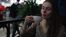 Mujer joven que se sienta en el café y el té de consumición Alameda de compras en fondo borroso almacen de metraje de vídeo