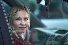 Mujer joven que se sienta en el coche Imagen de archivo libre de regalías