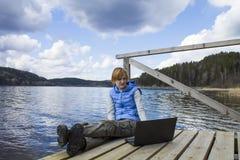 Mujer joven que se sienta en el embarcadero con el ordenador portátil Fotografía de archivo