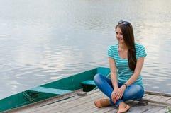Mujer joven que se sienta en el embarcadero y la sonrisa Imagenes de archivo