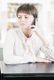 Mujer joven que se sienta en el escritorio con el teléfono Fotografía de archivo libre de regalías