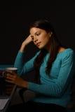 Mujer joven que se sienta en el escritorio en soñar despierto oscuro Imágenes de archivo libres de regalías