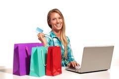 Mujer joven que se sienta en el escritorio que hace compras en línea Fotos de archivo libres de regalías