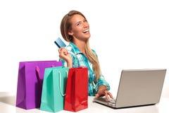 Mujer joven que se sienta en el escritorio que hace compras en línea Imagenes de archivo