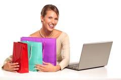 Mujer joven que se sienta en el escritorio que hace compras en línea Imagen de archivo libre de regalías