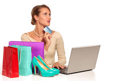 Mujer joven que se sienta en el escritorio que hace compras en línea Imágenes de archivo libres de regalías