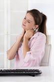 Mujer joven que se sienta en el escritorio que hace dolores en el cuello o hincharse Imagen de archivo
