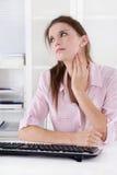 Mujer joven que se sienta en el escritorio que hace dolores en el cuello o hincharse Foto de archivo