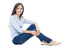 Mujer joven que se sienta en el fondo blanco Fotos de archivo libres de regalías