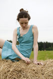Mujer joven que se sienta en el haystack Fotografía de archivo libre de regalías