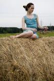 Mujer joven que se sienta en el haystack Fotografía de archivo