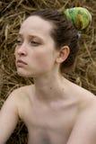 Mujer joven que se sienta en el haystack Imágenes de archivo libres de regalías