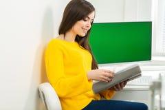 Mujer joven que se sienta en el lugar de trabajo y que lee el papel en oficina En el fondo es una pantalla verde foto de archivo libre de regalías