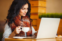 Mujer joven que se sienta en el ordenador portátil Imágenes de archivo libres de regalías
