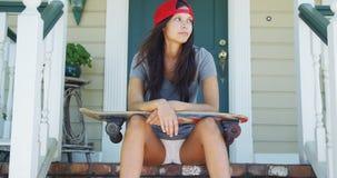 Mujer joven que se sienta en el pórtico con el monopatín Fotos de archivo libres de regalías