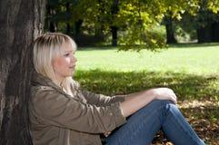 Mujer joven que se sienta en el parque Fotografía de archivo libre de regalías