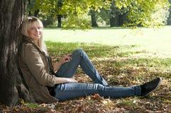 Mujer joven que se sienta en el parque Imagen de archivo libre de regalías