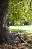 Mujer joven que se sienta en el parque Foto de archivo