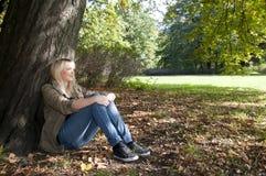 Mujer joven que se sienta en el parque Fotos de archivo