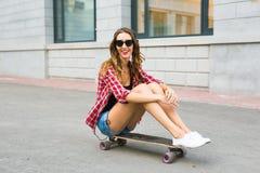 Mujer joven que se sienta en el patinador Mujer sonriente con el monopatín adentro al aire libre Fotos de archivo libres de regalías
