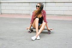 Mujer joven que se sienta en el patinador Mujer sonriente con el monopatín adentro al aire libre Fotografía de archivo