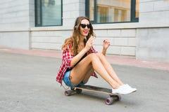 Mujer joven que se sienta en el patinador Mujer sonriente con el monopatín adentro al aire libre Imagenes de archivo