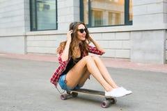Mujer joven que se sienta en el patinador Mujer sonriente con el monopatín adentro al aire libre Foto de archivo libre de regalías