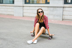 Mujer joven que se sienta en el patinador Mujer sonriente con el monopatín adentro al aire libre Imagen de archivo