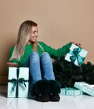Mujer joven que se sienta en el piso cerca del árbol de navidad del abeto y que sueña sobre presente, futuro, regalos y esperar u fotografía de archivo libre de regalías