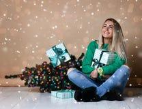 Mujer joven que se sienta en el piso cerca del árbol de navidad del abeto y que sueña sobre presente, los regalos y esperar un mi imagen de archivo libre de regalías