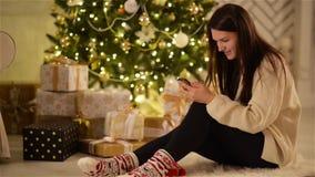 Mujer joven que se sienta en el piso con Smartphone negro en el árbol de navidad del fondo Morenita hermosa sonriente con metrajes