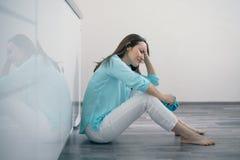 Mujer joven que se sienta en el piso de la cocina que lleva a cabo su cabeza y que llora, trastorno, triste, deprimido fotos de archivo libres de regalías