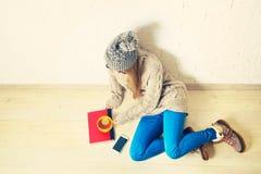 Mujer joven que se sienta en el piso de madera con un té Fotografía de archivo libre de regalías
