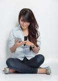 Mujer joven que se sienta en el piso mientras que hace algo con ella Imágenes de archivo libres de regalías