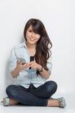 Mujer joven que se sienta en el piso mientras que hace algo con ella Fotografía de archivo libre de regalías