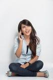 Mujer joven que se sienta en el piso mientras que llama con su smartpho Fotografía de archivo