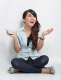 Mujer joven que se sienta en el piso mientras que sorpresa que mira para arriba al co Fotos de archivo libres de regalías