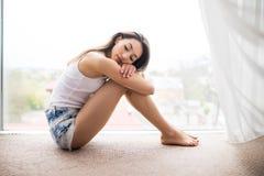 Mujer joven que se sienta en el piso que abraza sus rodillas, mirando a través de ventana integral la ciudad grande Imagen de archivo libre de regalías