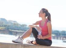 Mujer joven que se sienta en el riverbank Fotos de archivo
