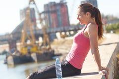 Mujer joven que se sienta en el riverbank imagenes de archivo