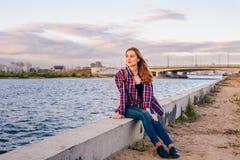 Mujer joven que se sienta en el riverbank fotografía de archivo