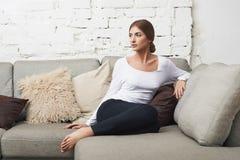 Mujer joven que se sienta en el sofá Imagen de archivo libre de regalías