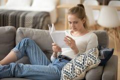 Mujer joven que se sienta en el sofá acogedor y que lee el libro de papel solamente imagen de archivo libre de regalías
